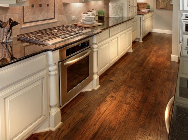 Kitchen with dark wood flooring and white cabinets
