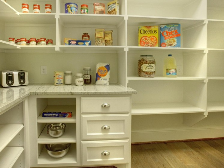 Pantry with deep fixed shelving and countertop